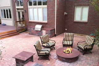 """Hardscape work is often a lot about driveways, walkways and patios, but some of the more exciting and dynamic installations we do are our custom outdoor brick paver fire pits. An outdoor fire pit adds a touch of sophistication to any outdoor space and while it may seem like a luxury, it is a great investment that allows you to get more time and use out of your outdoor space. We are lucky here in Colorado to have pretty comfortable summer days, but those summer nights (particularly in the foothills and mountains) can get chilly! What better way to wrap up an afternoon BBQ than by gathering around the outdoor fire pit rather than having to head indoors. Outdoor fire pits aren't just for warming your hands on a chilly evening, they can also be a fun way to cook your food! From gently charred kebabs to gooey s'mores, a fire pit provides an engaging way for people of all ages to help in the """"kitchen"""". Outside of the inherent entertainment value, installing a brick paver fire pit also improves the value and appeal of your home. Just like other landscape and hardscape design, an outdoor fir pit is an investment in the value of your home should you decide to sell. It helps to set your home apart from the field. Outdoor fire pits offer it all: ambiance, entertainment and value – what more could you ask for? Give us a call today for an estimate for your new brick paver fire pit, we'll have you set up for more summer fun in no time!"""